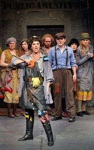 Penelope Pennywise (Kersten Rodau) with members of the URINETOWN company. Photo by Michal Daniel.